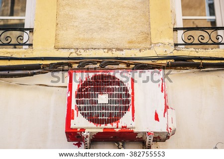 Air compressor installation on pedestal painted in different colors on a building wall - stock photo