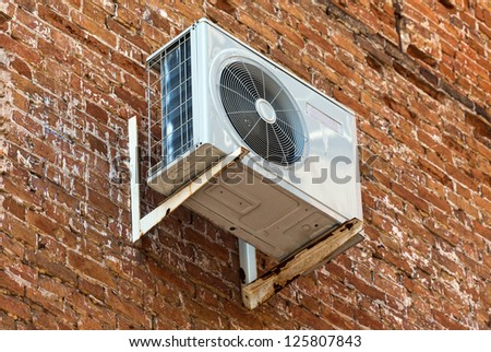 Air conditioning heat pump mounted on old brick wall - stock photo