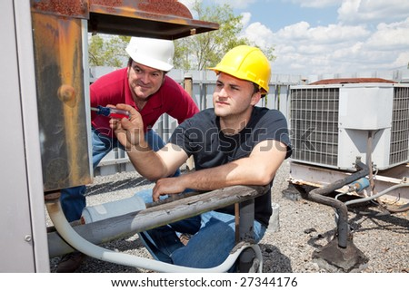 Air conditioning repair apprentice fixes an industrial compressor unit as his supervisor watches. - stock photo
