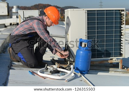 Air Conditioning Repair Young repairman on the roof fixing air conditioning system Model is actual electrician. - stock photo