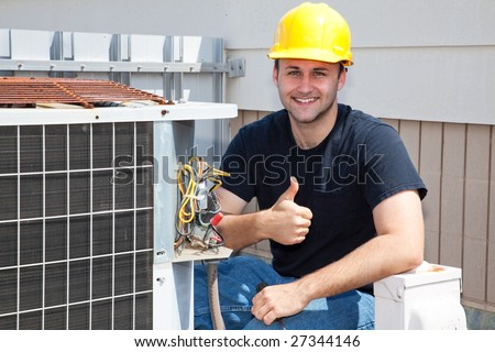 Air conditioning repairman working on a compressor and giving a thumbsup. - stock photo