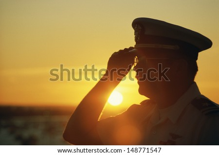AIR CRAFT CARRIER, NEW YORK - CIRCA 1986: Military officer saluting at sunset, NY - stock photo