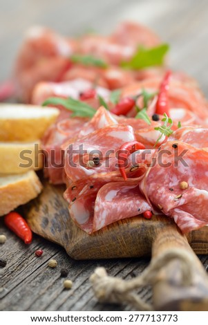 Air-dried Italian salami from Tuscany served on a wooden board with ciabatta bread - stock photo
