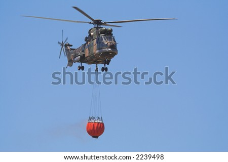 Air-Force Helicopter with a Bambi bucket filled to fight a forest fire - stock photo