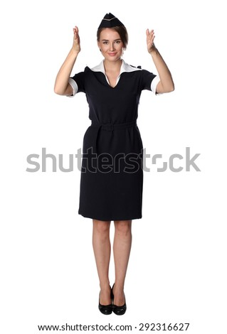 Air hostess in new uniform. Showing the way to emergency exit. - stock photo