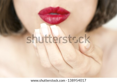 Air kiss from red lips,  pretty young woman lips blowing with open palm - stock photo