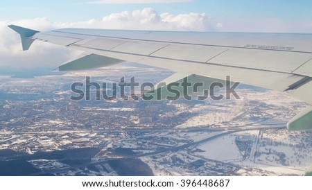 Air Plane wing through window with sky and city behind.  - stock photo
