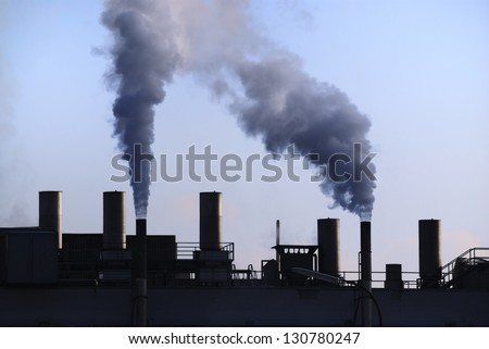 Air pollution - dirty smoke comming out of a chimney - stock photo
