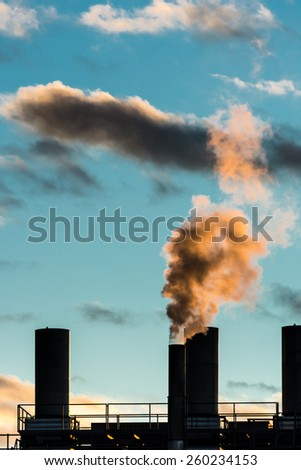 Air pollution from an smokestack - stock photo