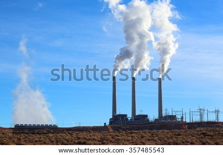 Air pollution from Industrial smoke stacks on a bright blue day - stock photo