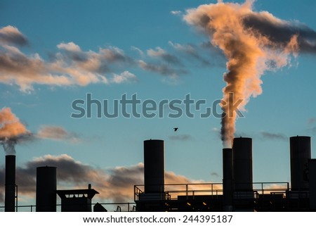Air pollution from smokestacks of a factory in the sunset. - stock photo