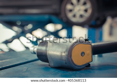 Air tools at car garage for checking a car brake system and wheel and tire. , process in vintage style - stock photo