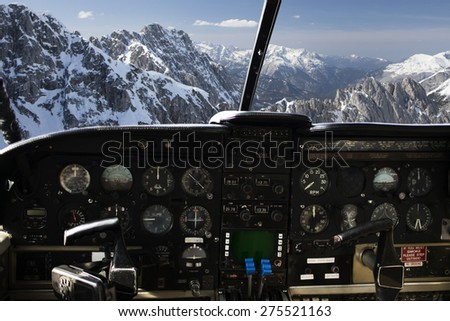 air transport, travel, technology and aviation concept - dashboard in airplane cockpit and view of snowy alps mountains behind windshield - stock photo