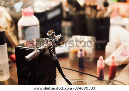 Airbrusher for professional makeup in a studio standing on a visagiste table. Cosmetics and brushes on the background. - stock photo