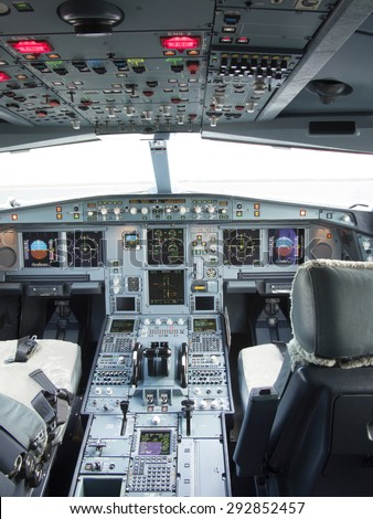 Airbus A330 airplane's cockpit with front,overhead and pedestrian panel taken on ground at day time with bright sunlit from windshield windows. - stock photo