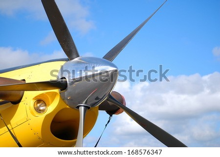 Aircraft detail of prop and spinner on yellow airplane.  It is a high-performance, five bladed propeller. The engine intake is positioned directly beneath the prop. It is a sunny day with a few clouds - stock photo