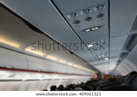 Aircraft interior with shallow focus on overhead signage and panel. Leading lines, and angled view giving impression of descent - stock photo