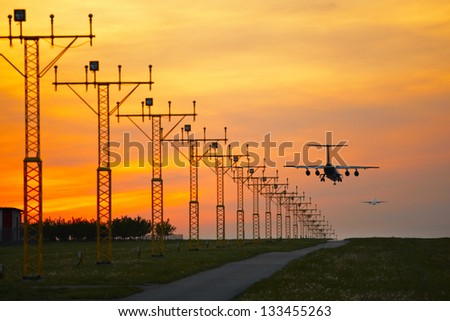 Aircraft is landing at the sunset - selective focus - stock photo