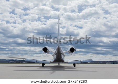 Aircraft learjet Plane in front of the Airport with cloudy sky - stock photo