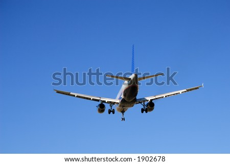 Aircraft with its landing gear down against a blue sky. - stock photo