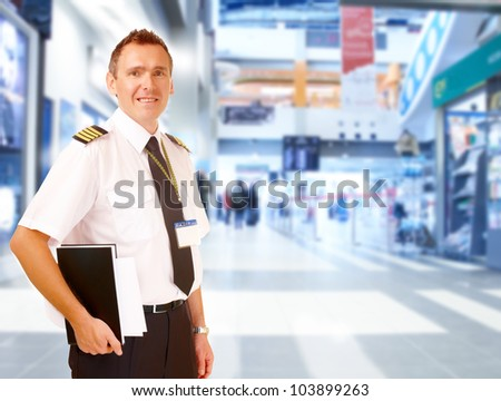Airline captain pilot wearing uniform with epaulettes standing at airport with his flight documents. - stock photo