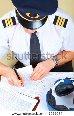 Airline pilot wearing hat, shirt with epaulets and tie filling in and checking papers flight plan, log book and weather forecast. Headset on the table. - stock photo
