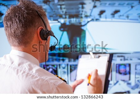 Airline pilot wearing uniform with epauletes and headset, writting on notepad inside airliner - stock photo