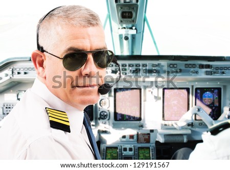 Airline pilot wearing uniform with epaulettes and headset working in airliner during flight. - stock photo