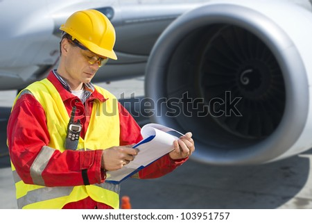 Airline safety engineer going through a pre-flight checklist - stock photo
