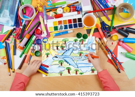 airliner fly high above the earth, child drawing, top view hands with pencil painting picture on paper, artwork workplace - stock photo