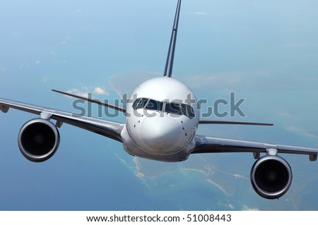 Airliner in flight with ocean and islands on the background - stock photo