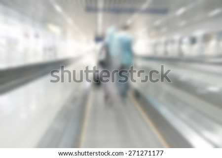 Airlines worker walk on escalator in defocused blur concept with vintage color style and effects. - stock photo