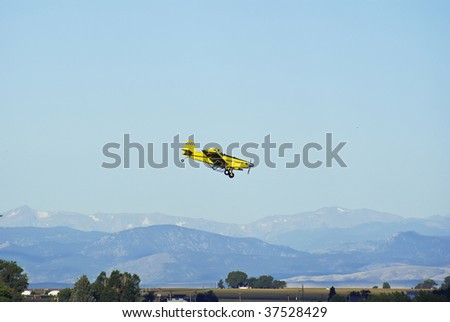 Airplane against the Rocky mountains making another run at a cornfield. - stock photo
