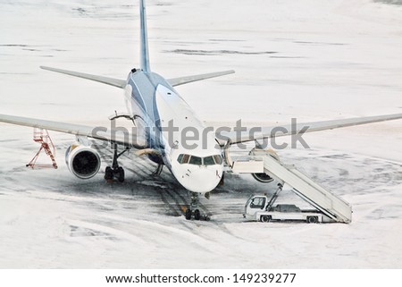 Airplane and servicing car at snowy airport - stock photo