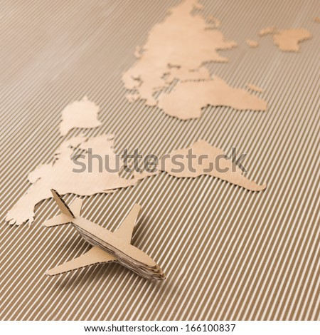 Airplane and world map made of cardboard. Square format, selective DOF. Delivery, shipping and logistic concept. - stock photo