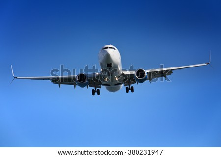 Airplane approaching airport - against clear blue sky - stock photo