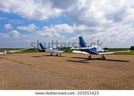 Airplane at airport with beautiful cloudscape in a background - stock photo