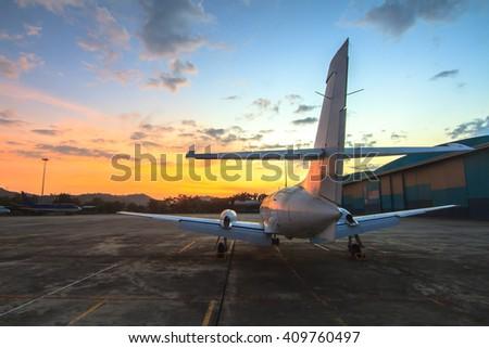 Airplane at sunrise - back lit - stock photo