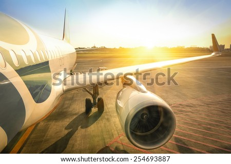 Airplane at terminal gate ready for takeoff - Travel concept and wander around the world in international airport at sunset - Warm saturated filter  - stock photo