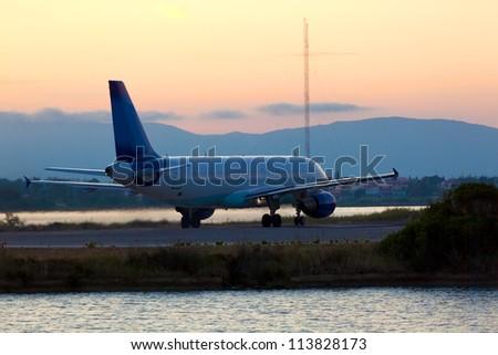 Airplane before take-off, evening scene, Corfu - stock photo