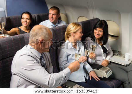 Airplane cabin businesspeople toasting with champagne flight travel passenger - stock photo