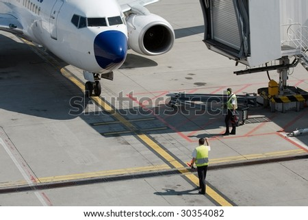 Airplane coming to it's parking stand at the airport - stock photo
