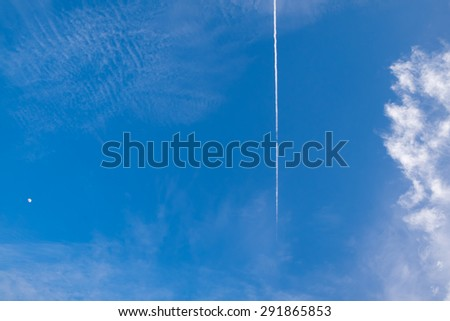 Airplane condensation trail or contrail with line of cloud over blue sky background and moon - stock photo