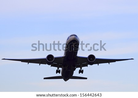 Airplane departing in the bright sky front view from below - stock photo