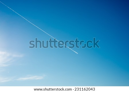 airplane flies in white clouds in a blue sky and leaving trail. - stock photo