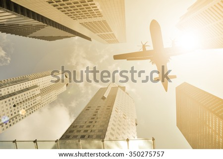 Airplane flight over modern building at afternoon. - stock photo