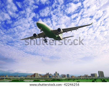 Airplane fly over buildings - stock photo
