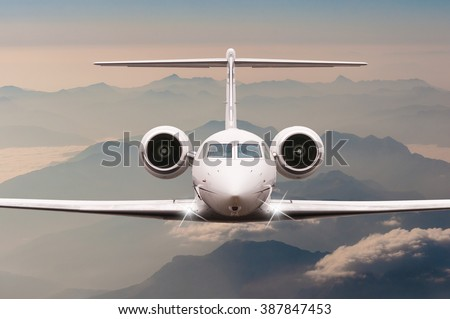 Airplane fly over clouds and Alps mountain on sunset. Front view of a big passenger or cargo aircraft, business jet, airline. Transportation, travel concept - stock photo