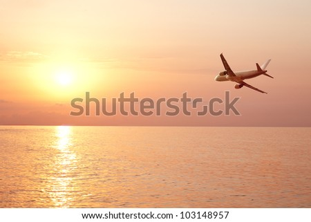 airplane fly over sea and sunset - stock photo