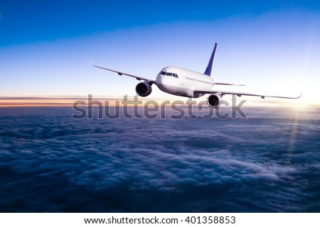 Airplane flying above clouds in dramatic sunset - stock photo